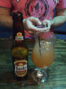 Can't decide? Have both. A cold Banks beer and a rum punch. But notice the phone - yes, I'm working. And yes, I AM wearing a pink shirt.