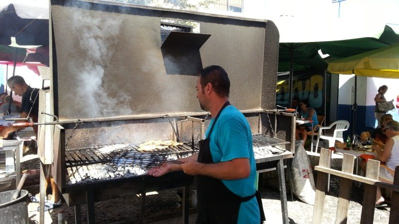 Grilling fresh fish at a local spot in Fuseta...