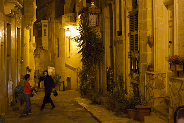 Two trick-or-treaters in the lonely nighttime streets of Birgu...