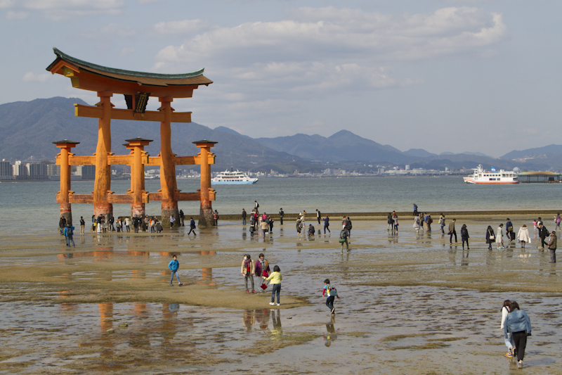 Visitors approach the torii at low tide...